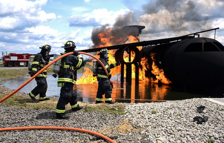 Fire fighters with the 87th Civil Engineer Squadron fire department prepare to put out a burning model aircraft during fire training on Joint Base McGuire-Dix-Lakehurst, New Jersey, June 3, 2019. The Fire training is used for Airmen completing their career development courses and for fire fighters to practice their skills in putting fires out while dealing with different weather elements. (U.S. Air Force photo by Airman 1st Class Ariel Owings)