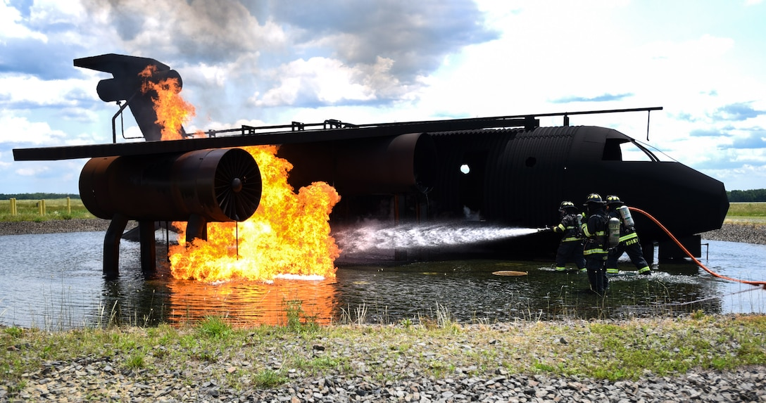 Fire fighters with the 87th Civil Engineer Squadron fire department work together to put out a fire during fire training on Joint Base McGuire-Dix-Lakehurst, New Jersey, June 3, 2019. The model aircraft fire is controlled by underground gas lines that can manipulate the size and intensity of the fire. (U.S. Air Force photo by Airman 1st Class Ariel Owings)
