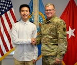 Ning Cao, a former DLA Troop Support intern, left, poses with Army Brig. Gen. Mark Simerly, DLA Troop Support Commander, right, at the DLA Troop Support June 6, 2019 in Philadelphia.