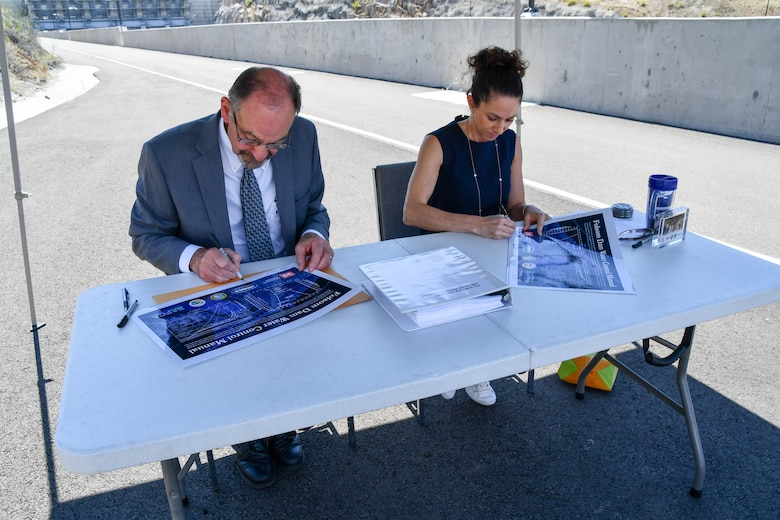 man and woman sign document