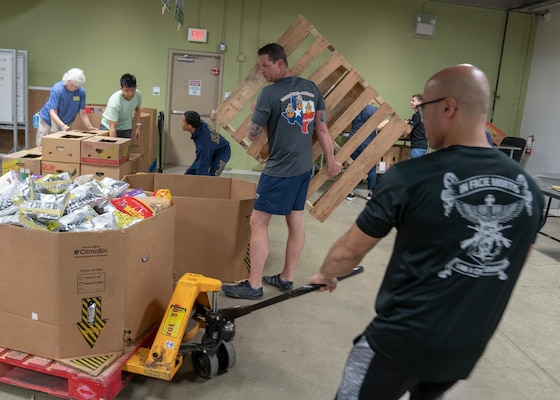 Petty Officer 2nd Class Mickael Cruz (right) and Senior Chief Petty Officer Casey Potvin (center), from Navy Medicine Education, Training and Logistics Command Academics Department, move pallets of food at the San Antonio Food Bank during a volunteer community outreach event June 11. The outreach event was part of the Navy's Sailor 360, a command-level program for junior enlisted, senior enlisted and junior officers, designed to strengthen and develop leadership through outreach events, classroom discussions and physical training.