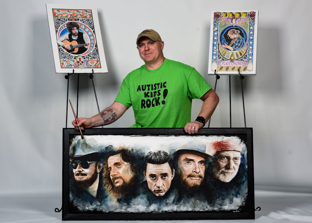 U.S Air Force Tech. Sgt. Isaac Denton, 66th Training Squadron Survival, Evasion, Resistance and Escape specialist, poses with his artwork at Fairchild Air Force Base, Washington, May 29, 2019. Denton has raised over $40,000 selling his paintings and donating the earnings toward raising Autism Awareness. (U.S. Air Force photo by Airman 1st Class Lawrence Sena)