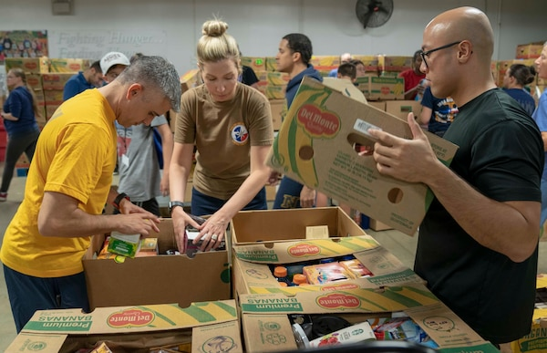 Petty Officer 1st Class Raynier Cruzborroto, Lt. Kimberly Melin (center), and Petty Officer 2nd Class Mickael Cruz (right), assigned to Navy Medicine Education, Training and Logistics Command, sort drinks during a volunteer community outreach event at the San Antonio Food Bank June 11. The outreach event was part of the Navy's Sailor 360, a command-level program for junior enlisted, senior enlisted and junior officers, designed to strengthen and develop leadership through outreach events, classroom discussions and physical training.