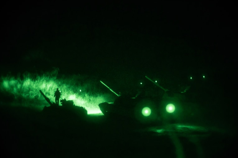A tank uses green headlights during a night training event.