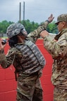 Army ROTC Cadet Shaunay Palmer, a student at Alabama A&M University, is coached into proper position to throw a test hand grenade during Advanced Camp, Cadet Summer Training, at Fort Knox, June 8, 2019. Cadets must first master throwing test hand grenades before moving on to throw a live hand grenade during the 31-day training camp. Advanced Camp is the most significant training evaluation event of Army ROTC, with the mission to assess a Cadet's potential to serve as a commissioned officer.
