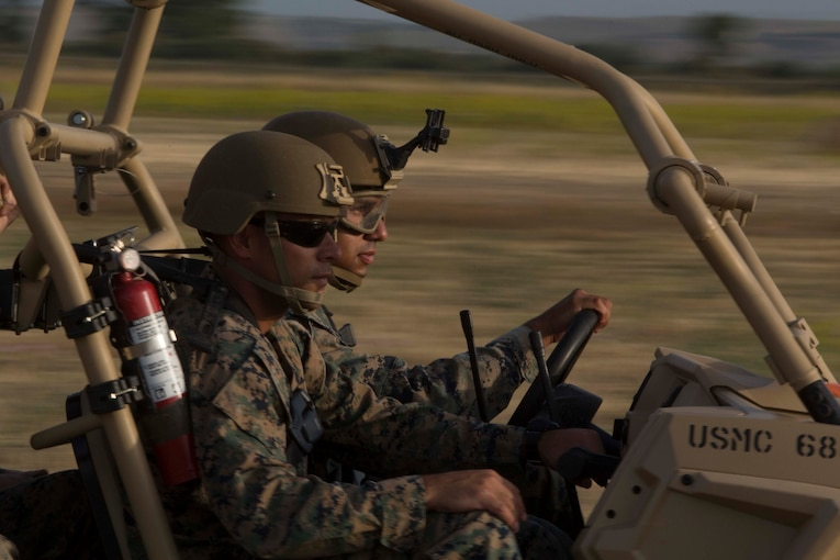 Marines wearing helmets drive an open-air vehicle against a blurry background.
