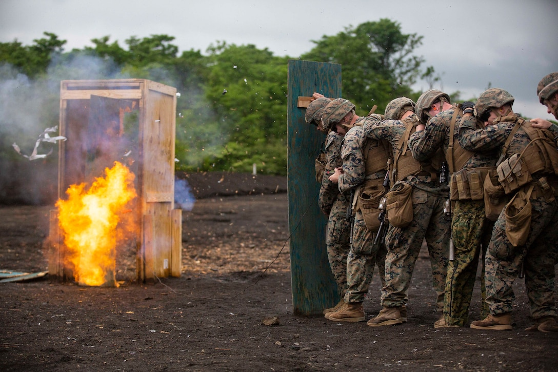 Six Marines stand single file behind a shield as a blast spreads fire, debris and smoke near a simulated doorway.