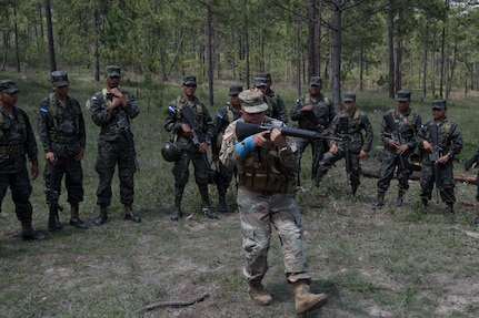 U.S. Army Staff Sgt. Roberto Santini, Puerto Rico National Guard Security Forces Training (SFT) instructor, demonstrates weapon-handling techniques to a group Honduran soldiers during the SFT course June 8, 2019, at the 1st Artillery Battalion in Zambrano, Honduras. Honduran Army soldiers participated in the two-week SFT course led by U.S. Army Puerto Rico National Guard service members assigned to Task Force ¬¬– Borinqueneer. The course taught them about security techniques and procedures to include formation, breaching, weapons training, casualty care, vehicle searching and tactical control points. The training was hosted as way to strengthen the host nations counter threat ability. (U.S. Air Force photo by Staff Sgt. Eric Summers Jr.)