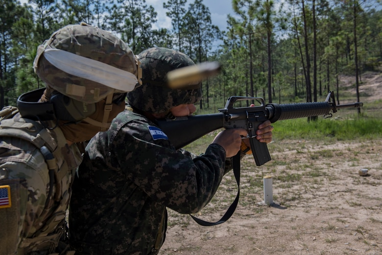 U.S. Army Sgt. Carlos Solver, Puerto Rico National Guard Security Forces Training (SFT) instructor, provides guidance to a Honduran soldier firing an M-16 rifle during the SFT course June 8, 2019, at the 1st Artillery Battalion in Zambrano, Honduras. Honduran Army soldiers participated in the two-week SFT course led by U.S. Army Puerto Rico National Guard service members assigned to Task Force ¬¬– Borinqueneer. The course taught them about security techniques and procedures to include formation, breaching, weapons training, casualty care, vehicle searching and tactical control points. The training was hosted as way to strengthen the host nations counter threat ability. (U.S. Air Force photo by Staff Sgt. Eric Summers Jr.)