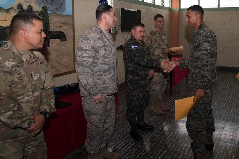 U.S. Army and Honduran military leadership congratulate graduates of the Security Forces Training course June 10, 2019, at the 1st Artillery Battalion in Zambrano, Honduras. Honduran Army soldiers participated in the two-week SFT course led by U.S. Army Puerto Rico National Guard service members assigned to Task Force ¬¬– Borinqueneer. The course taught them about security techniques and procedures to include formation, breaching, weapons training, casualty care, vehicle searching and tactical control points. The training was hosted as way to strengthen the host nations counter threat ability. (U.S. Air Force photo by Staff Sgt. Eric Summers Jr.)