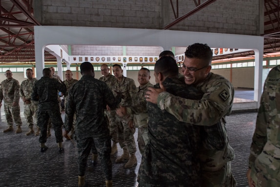 A U.S. Army and Honduran soldier shake hands embrace at the graduation of the Honduran Security Forces Training (SFT) course June 10, 2019, at the 1st Artillery Battalion in Zambrano, Honduras. Honduran Army soldiers participated in the two-week SFT course led by U.S. Army Puerto Rico National Guard service members assigned to Task Force ¬¬– Borinqueneer. The course taught them about security techniques and procedures to include formation, breaching, weapons training, casualty care, vehicle searching and tactical control points. The training was hosted as way to strengthen the host nations counter threat ability. (U.S. Air Force photo by Staff Sgt. Eric Summers Jr.)