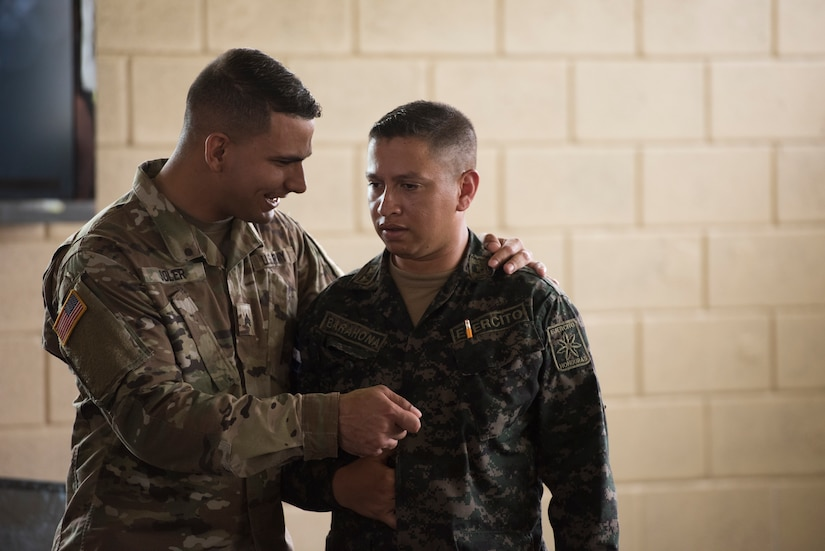 U.S. Army Sgt. Carlos Solver, Puerto Rico National Guard Security Forces Training (SFT) instructor, discusses graduation procedures with Honduran Army Commando 2 Edikson Barahona, 2nd Engineer Company general relations, during the SFT course June 8, 2019, at the 1st Artillery Battalion in Zambrano, Honduras. Honduran Army soldiers participated in the two-week SFT course led by U.S. Army Puerto Rico National Guard service members assigned to Task Force ¬¬– Borinqueneer. The course taught them about security techniques and procedures to include formation, breaching, weapons training, casualty care, vehicle searching and tactical control points. The training was hosted as way to strengthen the host nations counter threat ability. (U.S. Air Force photo by Staff Sgt. Eric Summers Jr.)