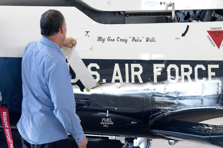 A member of the 12th Flying Training Wing unveils Maj. Gen. Craig Wills, 19th Air Force commander, name on the side of a T-6 Texan during the 19th Air Force change of command ceremony June 13, 2019, at Joint Base San Antonio-Randolph, Texas.  Wills comes to JBSA-Randolph from his previous assignment as the deputy chief of the Office of Security Cooperation-Iraq. (U.S. Air Force photo by Sean M. Worrell)