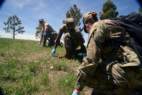 Airman 1st Class Amanda Deringer (right), Senior Airman Brian Williams (center), and other Airmen from the 341st Force Support Squadron, participate in a search and recovery exercise June 12, 2019, at Malmstrom Air Force Base, Mont. The exercise simulated an aircraft crash site, requiring the Airmen to search the terrain for any for remains of individuals or parts of the fictitious aircraft. (U.S. Air Force photo by Staff Sgt. Magen M. Reeves)