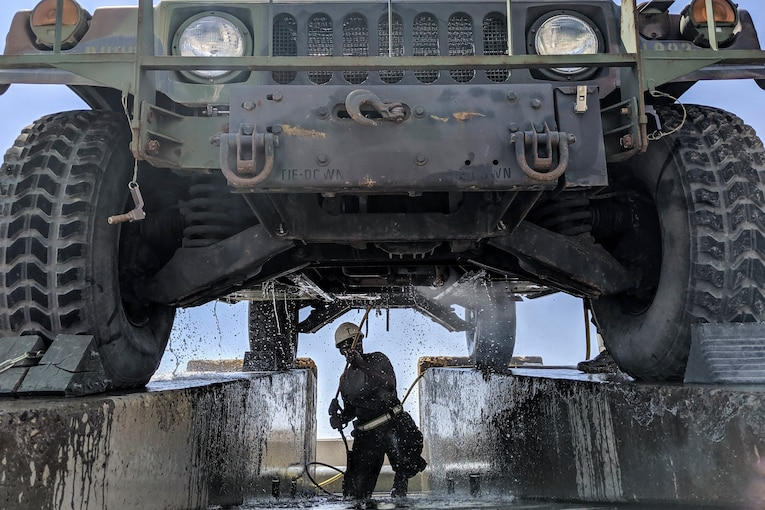 A soldier kneels underneath a military vehicle while spraying it with a hose.