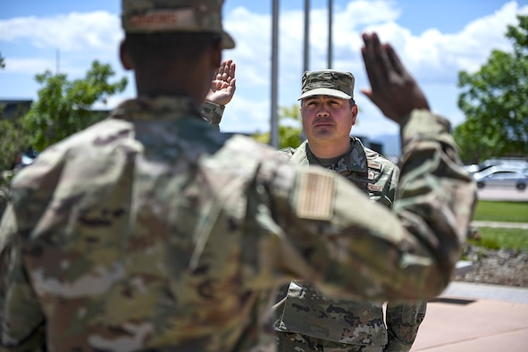 PETERSON AIR FORCE BASE, Colo. – Chief Master Sgt. Rodolfo Gamez (right), 21st Operations Group superintendent, recites the oath of enlistment during his re-enlistment ceremony administered by 2nd Lt. Jericho Simmons, June 6, 2019 at Peterson Air Force Base, Colo. Gamez has served in the U.S. Air Force for nearly 25 years and has been recently selected as the command chief of the 305th Air Mobility Wing at Joint Base McGuire-Dix-Lakehurst, N.J. Simmons graduated from the U.S. Air Force Academy one week prior to the ceremony and has a history with the 21st Space Wing as his father is the current 21 SW command chief. The moment was unique as it was the final re-enlistment for Gamez and the first time Simmons presided over this type of ceremony which symbolized the culmination of one career and the beginning of another.  (U.S. Air Force photo by Master Sgt. Sara Keller)