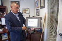 """Juan Rivera displays what he calls the """"crown jewel"""" of his accomplishments, a plaque proclaiming him as a founding member of the Department of Homeland Security. His work in creating the field of Cyber Security post 9/11 he said is his proudest accomplishment. Rivera now volunteers his time to help others to """"return the blessings I have received in my life."""""""