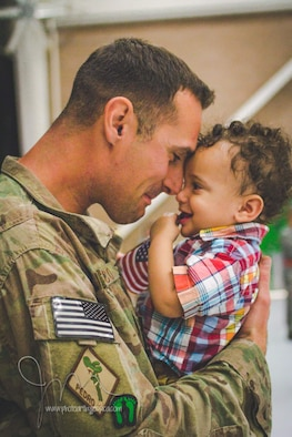 U.S. Air Force Tech. Sgt. Joshua Cunico, 373rd Training Squadron military training unit flight chief, holds back tears when he sees his child, Joshua Jr., 1, after returning from a deployment to Afghanistan in October 2014 at Davis-Monthan Air Force Base, Arizona. Cunico and his family cherish Father's Day this year because they get to spend it together. Cunico has deployed twice since becoming a dad in 2014. (Courtesy photo)