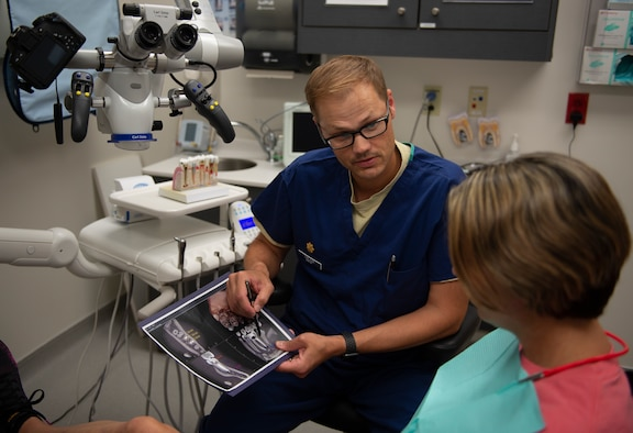 U.S. Air Force Maj. Timothy Carlson, 81st Dental Squadron endodontic resident, explains the root canal procedure to Regina Yarbrough, patient, in the Keesler Dental Clinic here, June 11, 2019. Carlson ensures his patient understands the procedure as well as other options, so they may make an informed decision. (U.S Air Force photo by Airman 1st Class Kimberly Mueller)