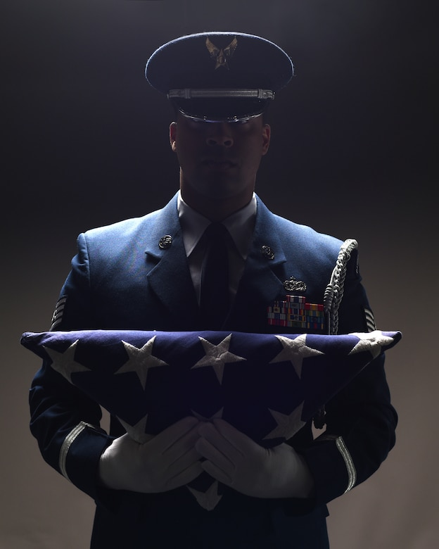 Staff Sgt. Alonzo Clark, 319th Air Base Wing Honor Guard program manager, holds a folded flag of the United States of America to his chest June 5, 2019, on Grand Forks Air Force Base, North Dakota. Clark acted as program manager for two years, with prior experience in the 319th Security Forces Squadron. (U.S. Air Force photo illustration by Senior Airman Elora J. Martinez)