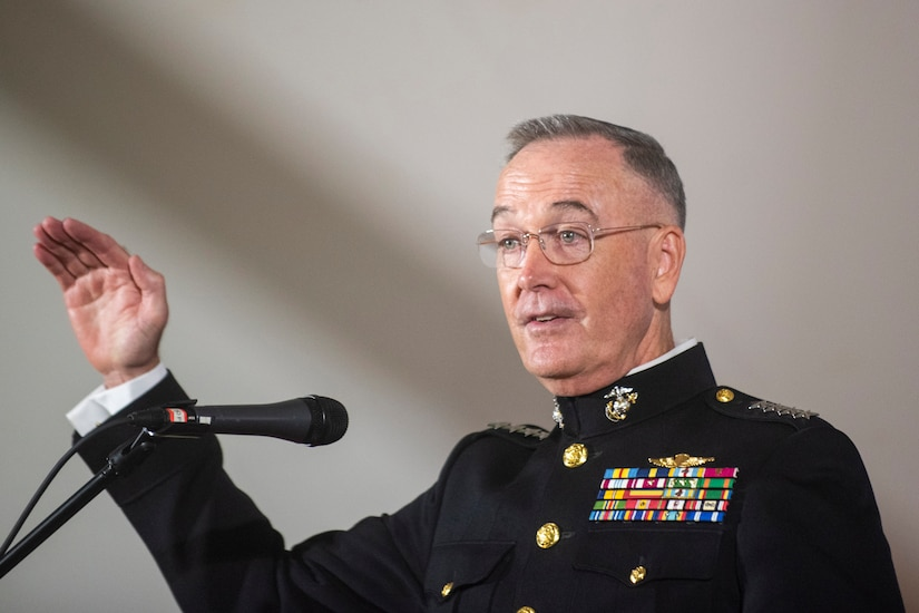 A general raises his hand while standing and speaking into a microphone.