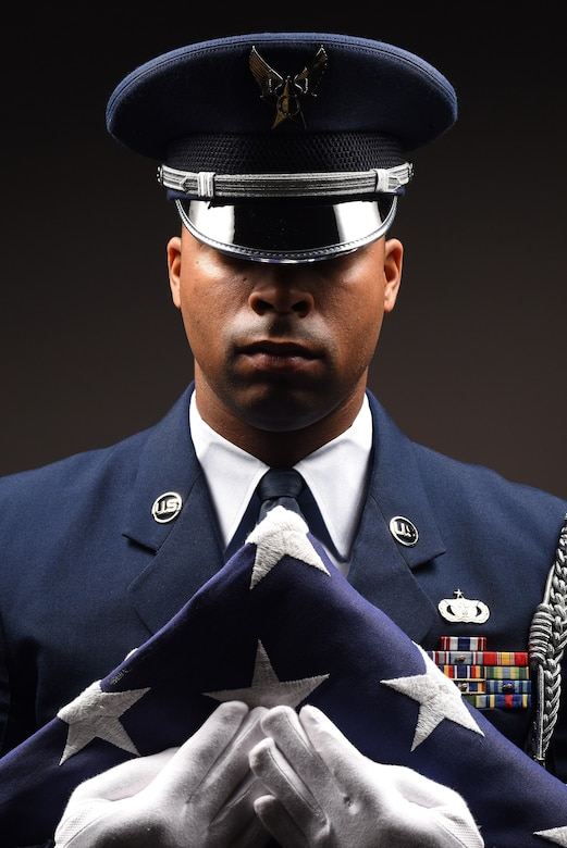 Staff Sgt. Alonzo Clark, 319th Air Base Wing Honor Guard program manager, grips a folded flag of the United States of America to his chest June 5, 2019, on Grand Forks Air Force Base, North Dakota. Clark manages the small, eight-person team of airmen on base, which has regional responsibility of 153,000 square-miles, to include North Dakota, Minnesota, Michigan and Wisconsin. Becoming a guardsman is an earned position of honor and duty, reserved only for members who strive to preserve the U.S. Air Force heritage. (U.S. Air Force photo illustration by Senior Airman Elora J. Martinez)