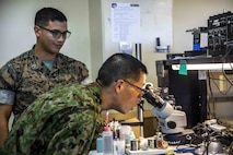 U.S. Marine Corps Staff Sgt. Joshua Coffill, left, shows Japanese Ground Self-Defense Force Sgt. Masaki Tetusuda, right, a broken motherboard through a microscope during a community exchange program tour on Camp Kinser, Okinawa, Japan June 7, 2019. During the tour, hosted by Combat Logistics Regiment 35, service members visited the base dining facility, supply management unit, a maintenance shop and the Battle of Okinawa historical display, before taking part in a social at the USO. The purpose of the program is to create bonds and increase operational understanding between the JGSDF and the U.S. Marine Corps. Coffill, a maintenance chief with CLR-35, 3rd Marine Logistics Group, is a native of San Diego, California. Tetusuda, is a native of Fukuoka, Japan.  (U.S. Marine Corps photo by Pfc. Courtney A. Robertson)