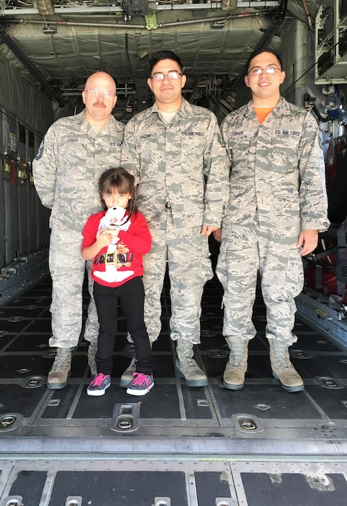 Airmen poise for a family photo in a C-130