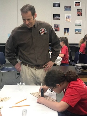 Transatlantic Middle East District civil engineer Ted Upson, aka Gator, discusses design strategies with students from Sacred Heart Academy during their week-long adventure at STARBASE Academy Winchester.