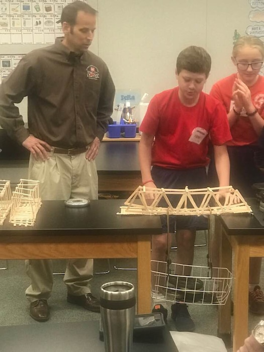 Transatlantic Middle East District's civil engineer Ted Upson assists students with the weight bearing test following their bridge build project at the STARBASE Academy Winchester.