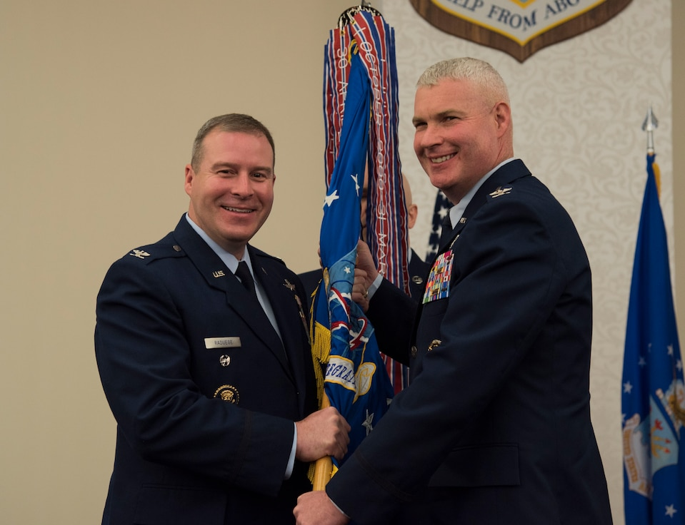 Colonel Chad D. Raduege, Director of Cyberspace and Information Dominance, presents the Air Force Network Integration Center guidon to Colonel Marc L. Packler during a change of command ceremony June 13 at Scott Air Force Base, Ill. Colonel Packler arrived from Scott Air Force Base, Ill, where he served as the 375 Communications Group Commander.