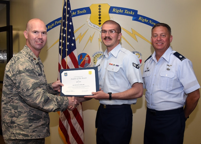 U.S. Air Force Maj. Kevin Boss, 17th Training Group director of operations, presents the 316th Training Squadron Student of the Month award to Airman 1st Class Ryan Cieslak, 316th TRS student, at the Brandenburg Hall on Goodfellow Air Force Base, Texas, June 7, 2019. The 316th TRS's mission is to conduct U.S. Air Force, U.S. Army, U.S. Marine Corps, U.S. Navy and U.S. Coast Guard cryptologic, human intelligence and military training. (U.S. Air Force photo by Airman 1st Abbey Rieves/Released)