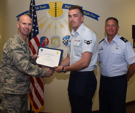 U.S. Air Force Maj. Kevin Boss, 17th Training Group director of operations, presents the 315th Training Squadron Student of the Month award to Airman 1st Class Ryan Keenen, 315th TRS student, at the Brandenburg Hall on Goodfellow Air Force Base, Texas, June 7, 2019. The 315th TRS's vision is to develop combat-ready intelligence, surveillance and reconnaissance professionals and promote an innovative squadron culture and identity unmatched across the U.S. Air Force. (U.S. Air Force photo by Airman 1st Class Abbey Rieves/Released)