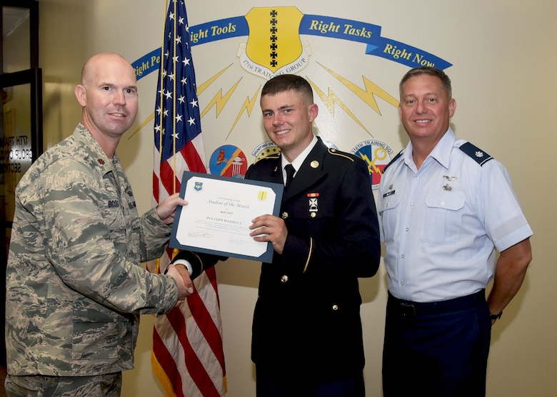 U.S. Air Force Maj. Kevin Boss, 17th Training Group director of operations, presents the 312th Training Squadron Student of the Month award to U.S. Army PVT Cody Wambolt, 312th TRS student, at the Brandenburg Hall on Goodfellow Air Force Base, Texas, June 7, 2019. The 312th TRS's mission is to provide Department of Defense and international customers with mission ready fire protection and special instruments graduates and provide mission support for the Air Force Technical Applications Center. (U.S. Air Force photo by Airman 1st Class Abbey Rieves/Released)