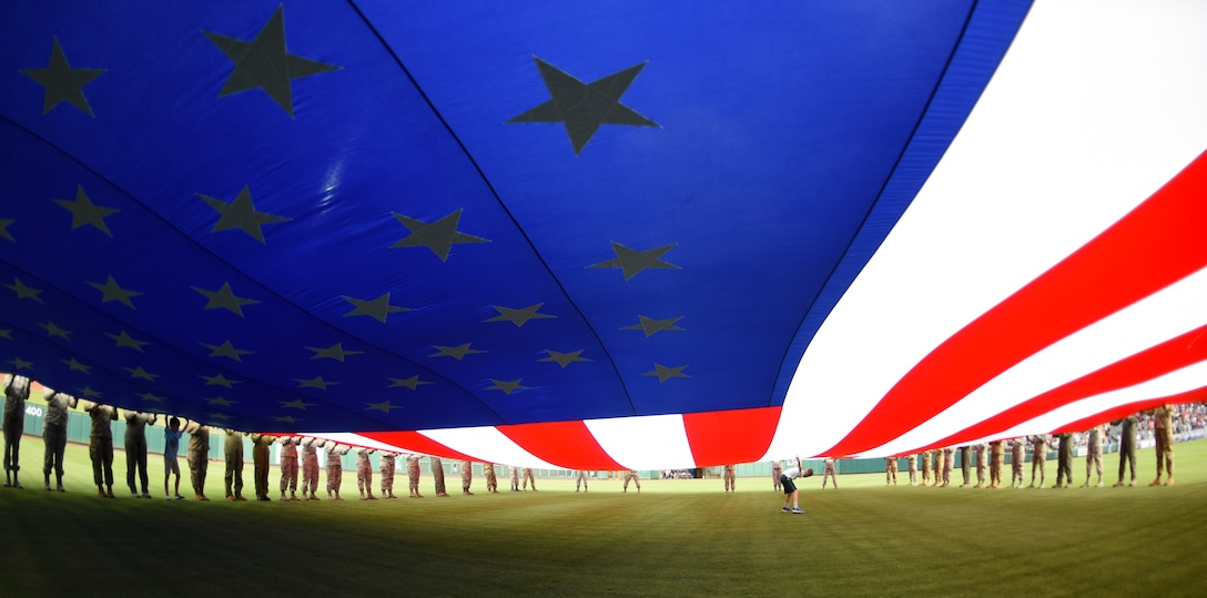 A giant American flag is held in place by military members from multiple United States service brances as well as Canadian Air Force members assigned to the 552nd Air Control Wing during the Oklahoma City Dodgers Military Appreciation Night May 17, 2019, Oklahoma City, Oklahoma. Proper display, handling and disposal of the flag is part of etiquette taught to military members throughout their careers. (U.S. Air Force photo/Greg L. Davis)