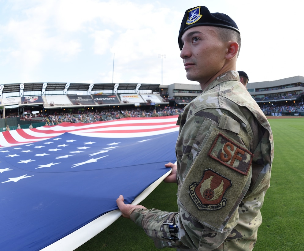 A member of the 72nd Security Forces Squadron helps hold a giant American flag in place during the opening ceremonies of an Oklahoma City Dodgers minor league baseball game during Military Appreciation Night May 17, 2019, Oklahoma City, Oklahoma. Proper display, handling and disposal of the flag is part of etiquette taught to military members throughout their careers. (U.S. Air Force photo/Greg L. Davis)