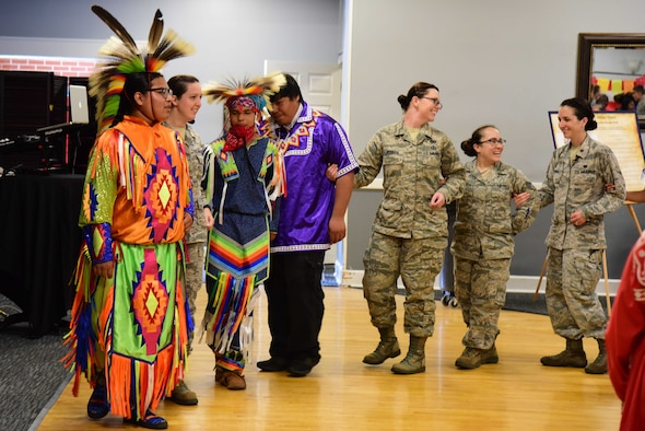 Choctaw dancers joined by military members lock arms for the festivities at Diversity Day, June 7, 2019, on Columbus Air Force Base, Miss. The Choctaw Dancers asked the attendees to get involved in a few of their traditional dances to get the community involved in their traditions. (U.S. Air Force photo by Elizabeth Owens)