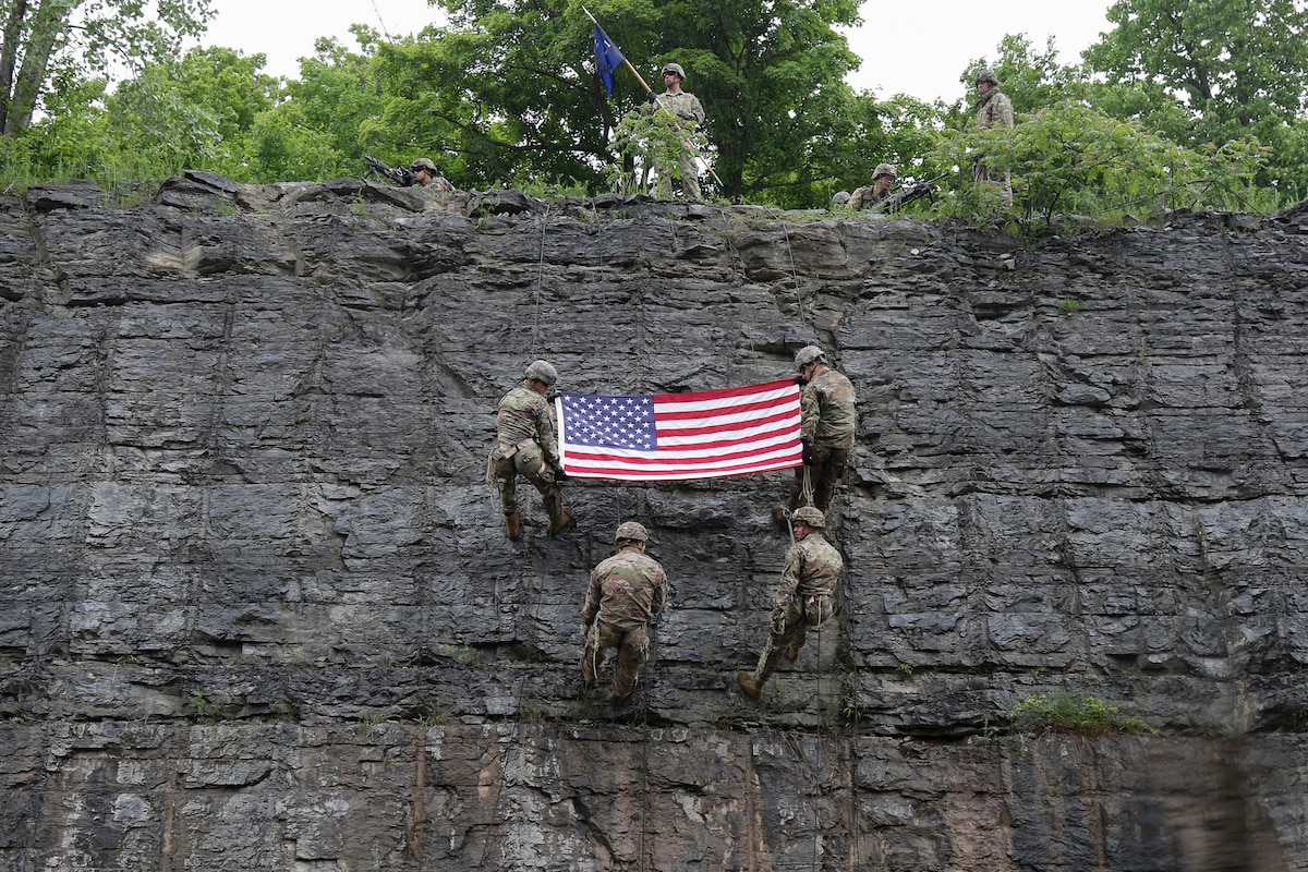 Two soldiers holding an American flag rappel down a rock face with others as more soldiers look on from the cliff top.