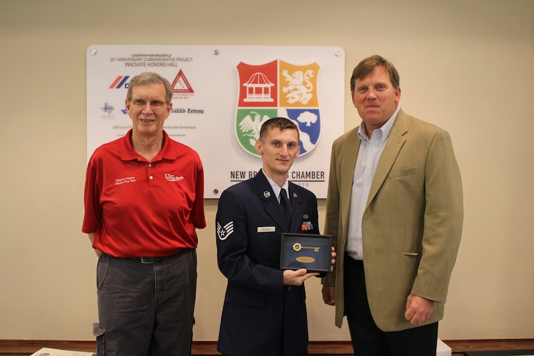 Staff Sgt. Nathan Lindgren, 502 Civil Engineer Squadron firefighter, receives the key to the city from New Braunfels Mayor Pro Tem Wayne Peters, left, and Mayor Barron Casteel during a ceremony on May 14 that honored Lindgren as the New Braunfels Chamber of Commerce Airman of the Quarter.