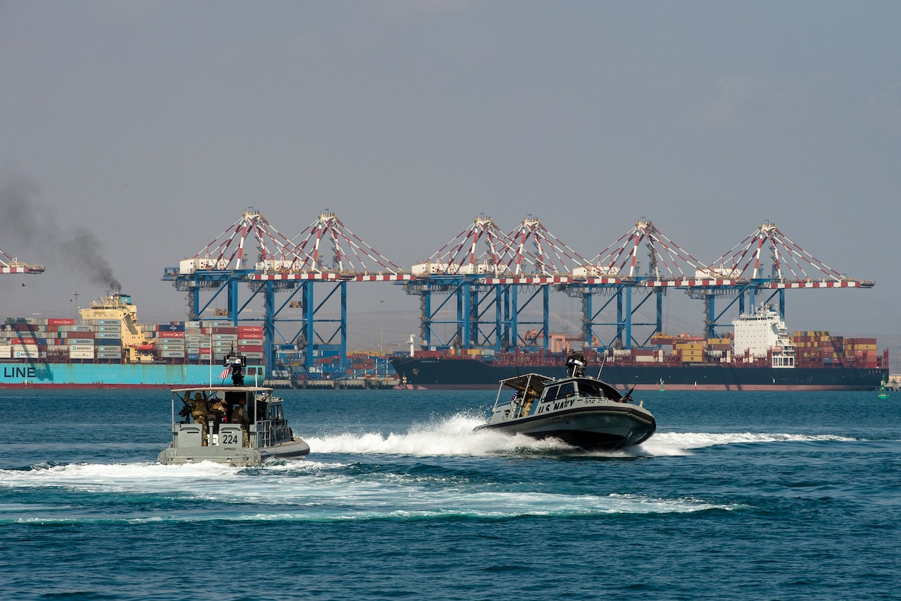 Two naval vessels speed through the water near a port. In the background are a half-dozen port cranes moving cargo from container ships.