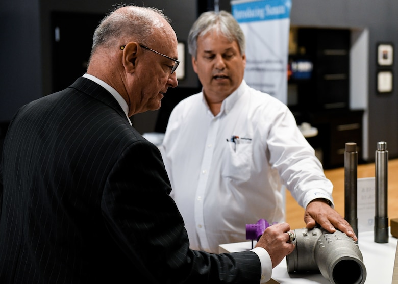 Retired Col. Joe Zeis, the Senior Advisor for Aerospace and Defense for the Ohio Governor's Office, inspects a T-pipe, used in 910th aerial spray missions, during a tour of America Makes, June 13, 2019.