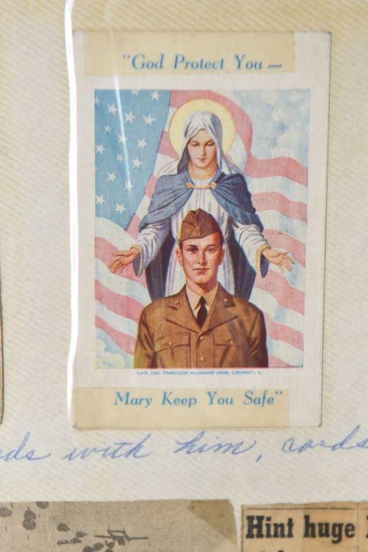 A religious card taped into a scrapbook compiled by Aida Bonsonto showcases her husband's military service during World War II.