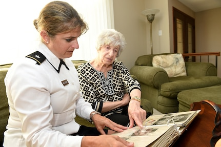 Brig. Gen. Kris A. Belanger, Commanding General, 85th U.S. Army Reserve Support Command looks at a scrapbook compiled by Aida Bonsonto of her husband's Army service during World War II.