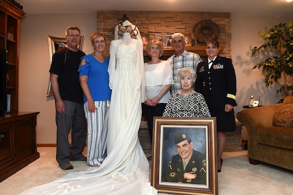 The family of Aida Bonsonto pauses for a photo with Brig. Gen. Kris A. Belanger, Commanding General, 85th U.S. Army Reserve Support Command and a wedding dress made from a World War II parachute that her husband sent home.