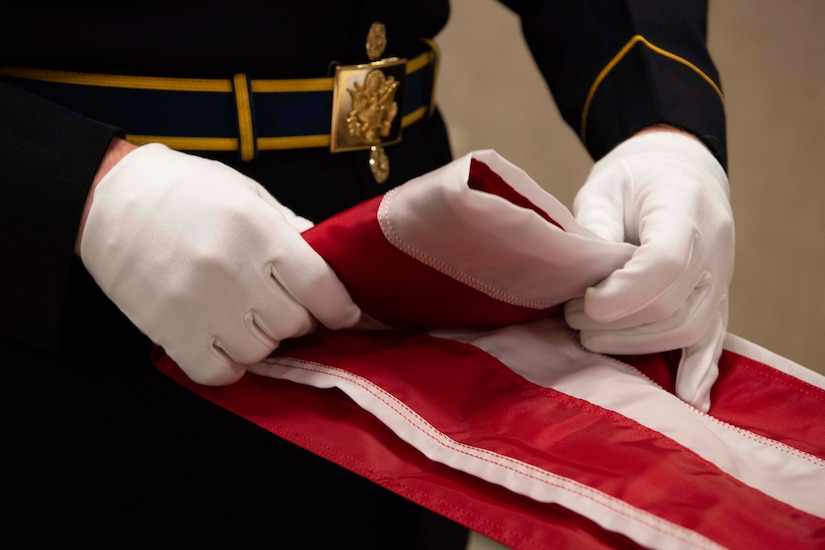 A soldier folds an American flag.