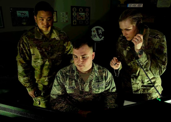 Maj. Andrew Hong, 32nd Weapons Squadron (WPS) phase manager and instructor, Capt. Stephen Baker, 32nd WPS Cyber Warfare Operations (CWO) Weapons Instructor Course (WIC) student, and Maj. Michelle Bostic, 32nd WPS CWO WIC student, look at computer monitors at the 32nd WPS on Nellis Air Force Base, Nev., June 10, 2019. The CWO WIC for Weapons School Integration (WSINT) has three main phases throughout the course including Defensive Cyber Operations (DCO), Offensive Cyber Operations (OCO) and integration phase. (U.S. Air Force photo by Airman 1st Class Bryan Guthrie)