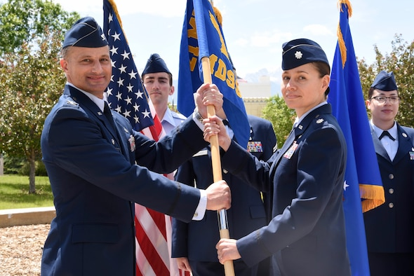 Col. Christopher Vaughn, 21st Medical Group commander, presents the guidon to Lt. Col. Lisa Guzman, 21st Medical Support Squadron commander, during a change of command ceremony, June 10, 2019 at Peterson Air Force Base, Colorado. The passing of the guidon represents a formal transfer of authority and responsibility from an outgoing commander to an incoming one. This ensures that the unit and its Airmen are never without leadership.  (U.S. Air Force photo by Staff Sgt. Alexandra M. Longfellow)