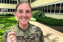 Spc. Kayla Adkins, 384th Military Police Company and Greenwood, Ind., native, is all smiles as she proudly displays a commander's challenge coin she received from Maj. Gen. David C. Coburn, U.S. Army Financial Management Command commanding general, during a ceremony celebrating both the 244th Army birthday and the 244th birthday of the Army Finance Corps at the Maj. Gen. Emmett J. Bean Federal Center in Indianapolis June 14, 2019. It is an Army tradition that the youngest Soldier available at an Army birthday celebration help the commander and sergeant major cut a cake, and Adkins was the youngest at 22 years old. (U.S. Army photo by Mark R. W. Orders-Woempner)