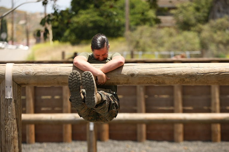A midshipman struggles to get over a log on an obstacle course.