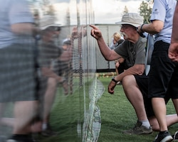 "Visitors of ""The Moving Wall,"" a half-size replica of the Vietnam Memorial that stands in Washington D.C., search for names of loved ones, friends, and comrades lost on the Vietnam War following the opening ceremony of the wall June 13, 2019 in Medical Lake, Wash. Visitors can view the display 24 hours a day at the 200 block of South Prentis St. in Medical Lake. (U.S. Air National Guard photo by Staff Sgt. Rose M. Lust/Released)"